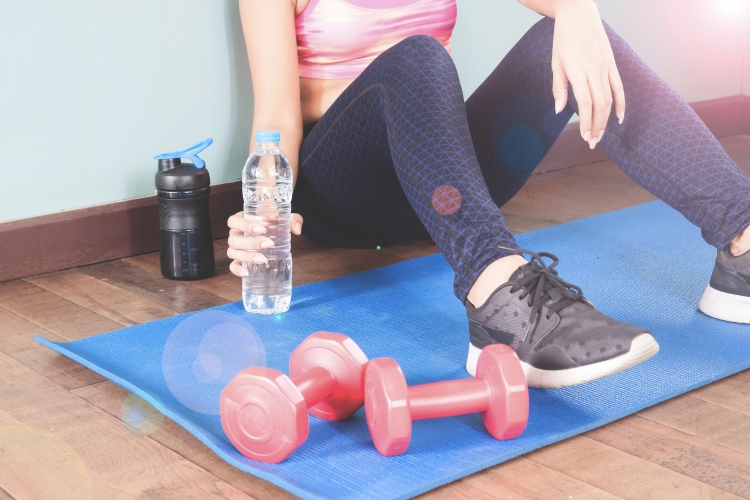 Fitness woman holding bottle of water after workout, Healthy lif